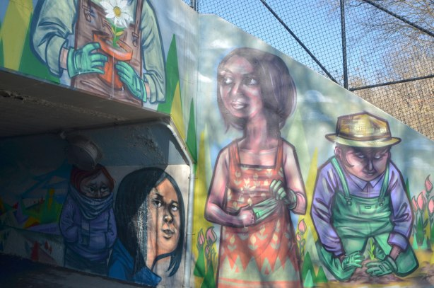 a mural by elicser on a railway underpass by the woodfield community rail garden, pictures of people gardening