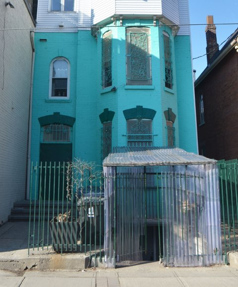 an old brick house painted turquoise with green trim. wrought iron fence in front. A corrugated plastic covering has been made to cover the entrance to the basement door. the covering comes out from the house to beyond the fence, all the way to the sidewalk