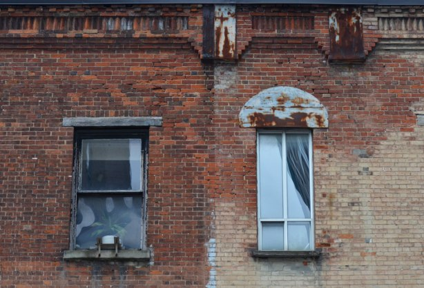 an old brick building with two windows.