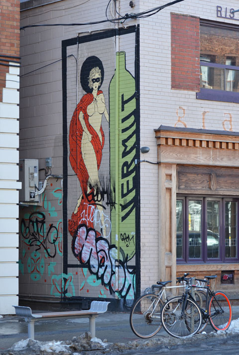a tall green bottle painted on the wall with the word vermut written vertically. Beside the bottle is painted a naked woman draped in red with breasts showing.
