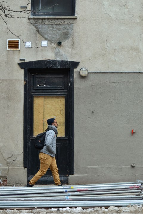 a man walks past a boarded up doorway
