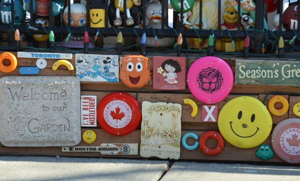 under a metal fence, a retaining wall that is covered with frisbees, plaques with words on them and other plastic bits