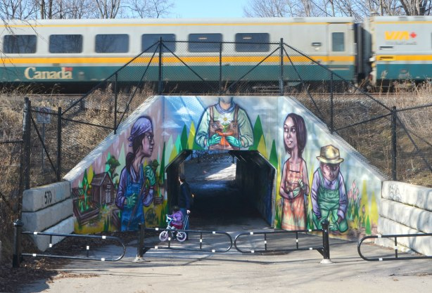 a mural by elicser on a railway underpass by the woodfield community rail garden that covers all the concrete of the opening. a VIA train passes overhead as a father and daughter stop to watch