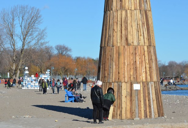 a woman pokes her head inside a hole in a tall wood structure on the beach, other art installations are in the background, lots of people, some people sitting on chairs.
