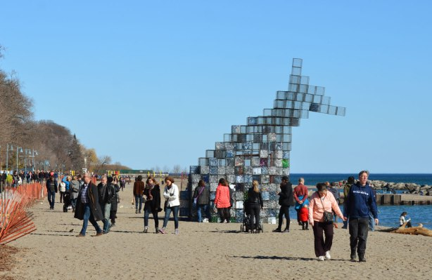 people looking at an art installation on the beach made of wire cage cubes stacked on top of each other. The ones on the bottom are filled with empty plastic bottles of different colours and shapes. The upper cages are empty and they are joined together to look like the head of a creature.