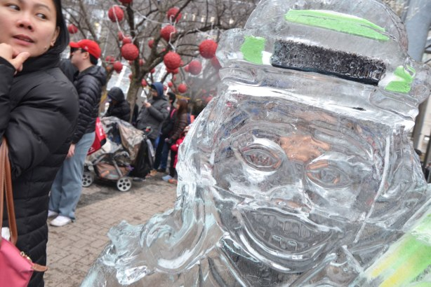 an ice sculpture of a face, perhaps a man weraing a hat with a black hat band?, crowd scene in the background, a woman's face on the left side of the photo.