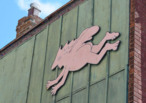 a wood cut out in pale pink, mounted high on an exterior green wall, naked person with wings and a funny shaped face