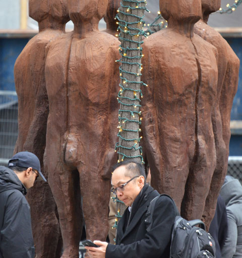wood sculpture of naked men in a circle with their backs inward, at Queen and Victoria streets, two men walking past the sculpture