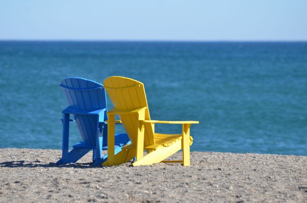 two empty muskoka chairs on the beach beside Lake Ontario on a sunny February day