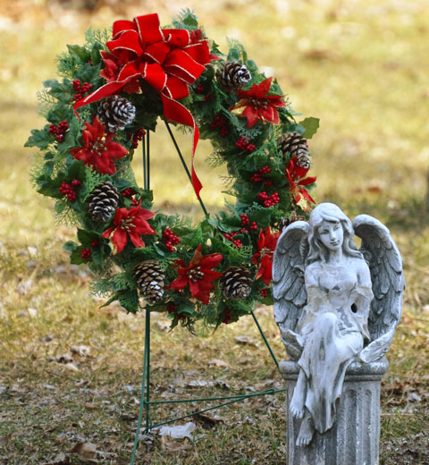 a small statue of an angel sitting on a pedestal in a cemetery, a Christmas wreath in green with red bows and brown pine cones is behind the angel.
