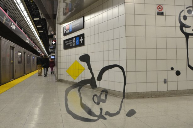 art on a subway platform, a line drawing of a very large apple that has been cut in half, on the wall and floor of the station