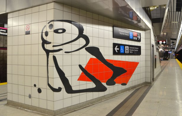 art on a subway platform wall, a salt or pepper shaker in black on white tiles
