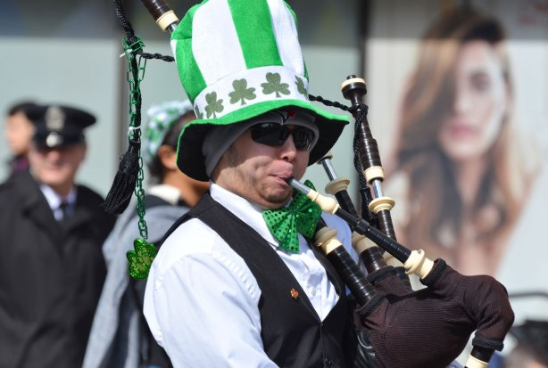 a man playing the bagpipes in a St. Patricks day parade. he's wearing an oversized green and white striped hat with a band of shamrocks on it. Also wearing a big green bowtie