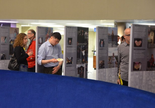 people looking at an exhibit of photos and stories that are printed on upright posters standing on the floor.
