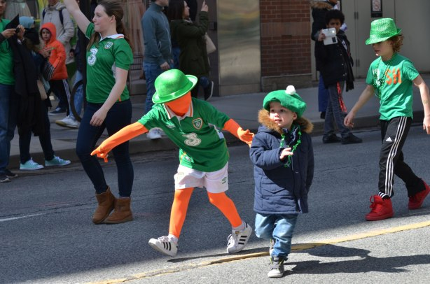 boys running a parade. one is wearing an orange body suit that also covers his face, also green tshirt and white shorts and green bowler.