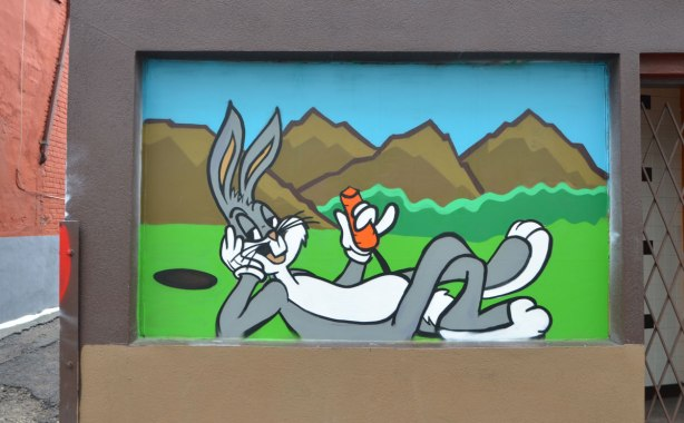 mural of bugs bunny lying on the ground, head on elbow, eating a carrot