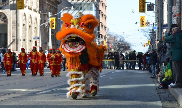 chinese dragon, with two people inside it working it, walking down the street in a parade with spectators standing on the sidewalk