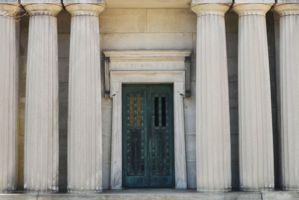 a metal door in a building in a cemetery, three large columns on each side of the door