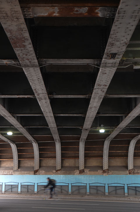 under a railway bridge, steel girders above, street passes under, across the street the lower part of the wall is blue tile, a man on a bicycle is passing by