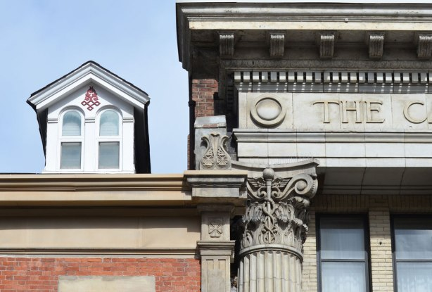 architectural details on an old bank building, a fancy column top (ionic?), some carvings in the stone work.