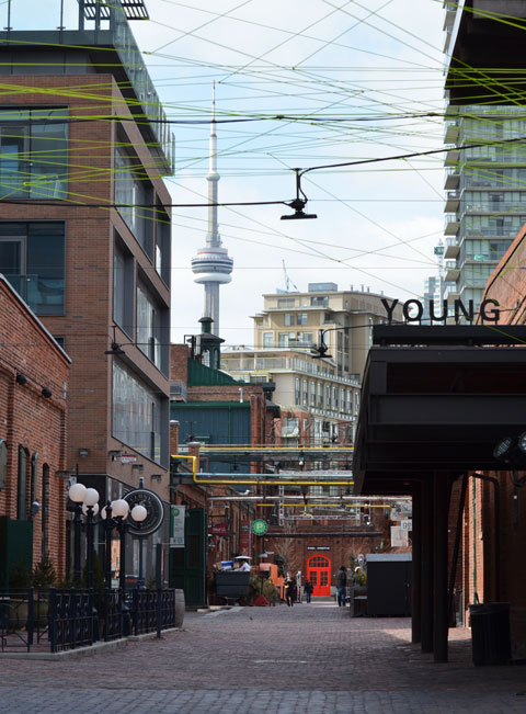 Cherry street entrance to the distrillery district, looking west towwards the CN tower, brick road, overhead lights, bright orange door in the background,