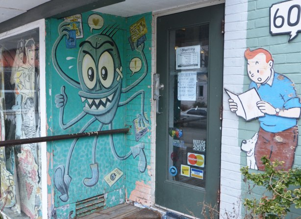 the door of a book store, with a cut out of Tintin beside it and a drawing of a creature with 4 legs and 4 arms, the hands are all holding something