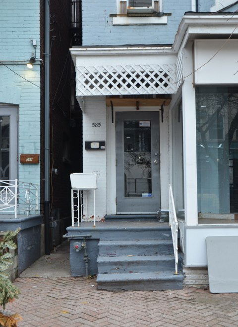 grey door, white porch, crooked grey steps