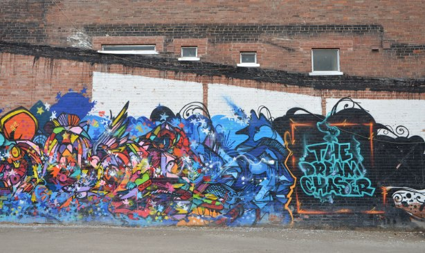 one end of a colourful mural with many shapes and colours, with the title of the mural, The Dream Chaser