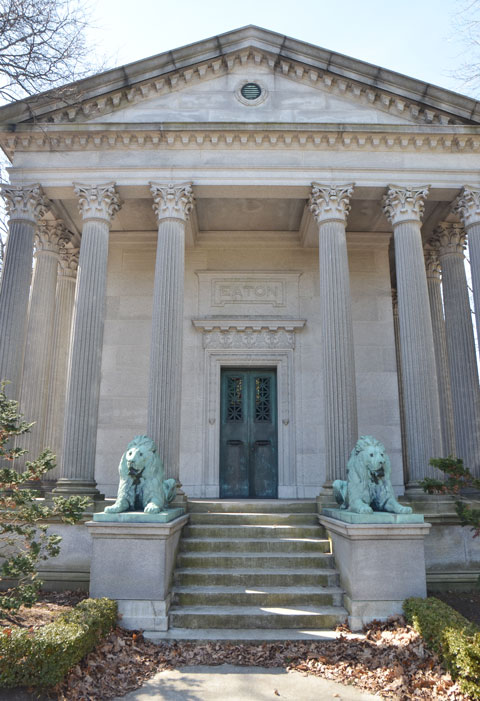 entrance to Eaton tomb/vault at Mt. Pleasant cemetery, two lions beside the steps that lead to the metal door, large corninthian columns on either side of the door.