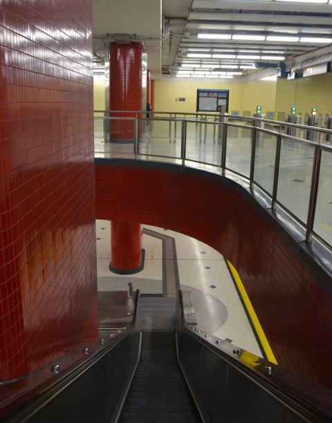 looking down the main escalator at Bessarion subway station, the upper level has yellow walls and the lower level (track level) can also be seen.