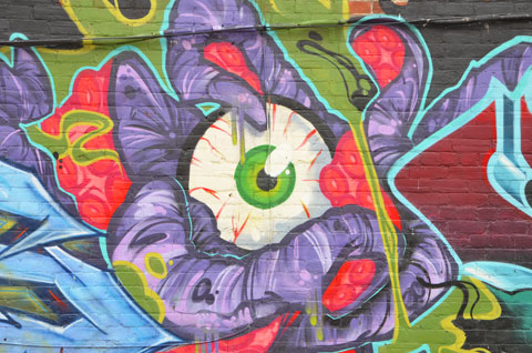big eyeball painted in the midlle of a mural