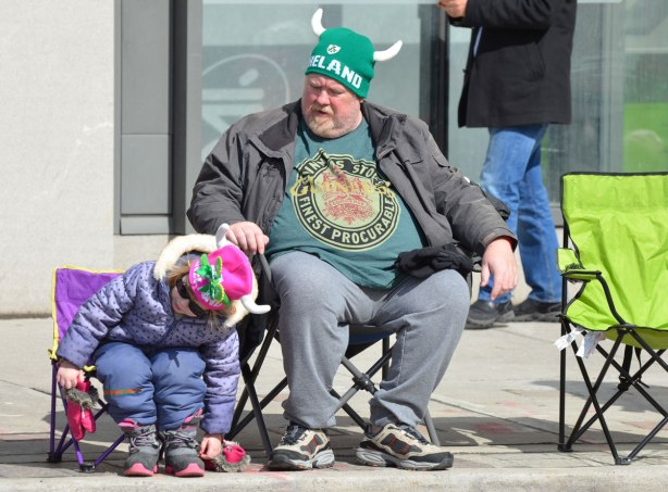 a father and daughter have seats on the sidewalk as they watch a parade go by