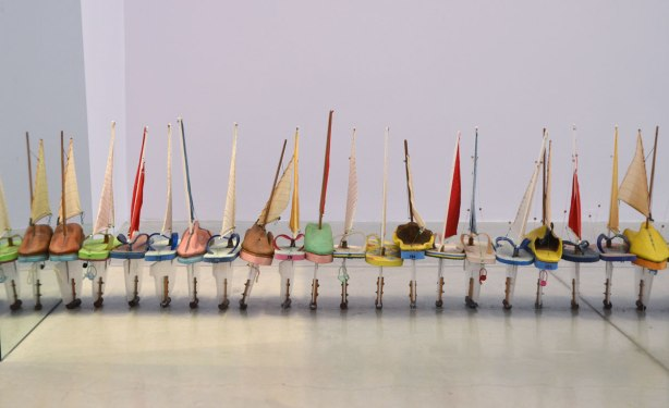 a line of little sailboats on the floor, all parallel to each other, the base of the boat (hull) is a flip flop or sandal.