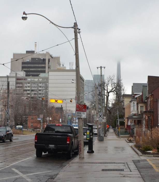 looking south on McCaul street towards the CN tower, the top of the tower is covered in low cloud.