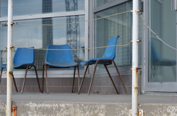 three old blue plastic chairs with metal rusty legs sit on the concrete porch of a commercial building. Windows behind them. one of the chairs is reflected in the window