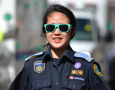 a girl wearing green sunglasses and a scout uniform