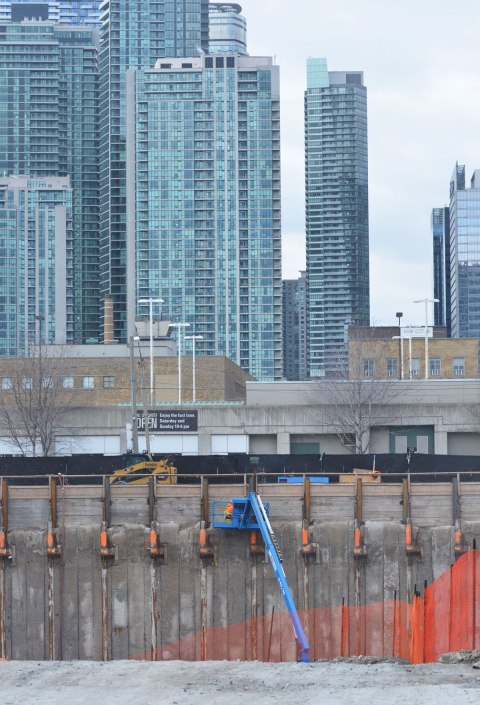 a blue crane inside a hole that is a construction site for a new condo, with many glass tower condos in the background.