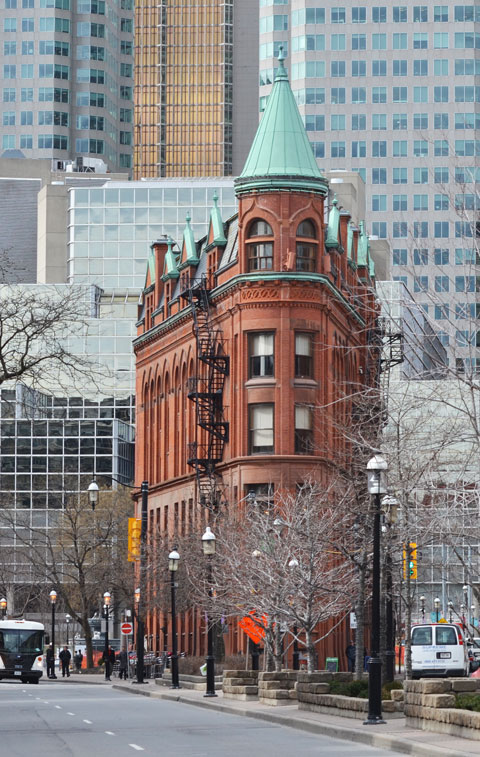 the Gooderham building, built in the flatiron style, with glass towers behind it, downtown Toronto