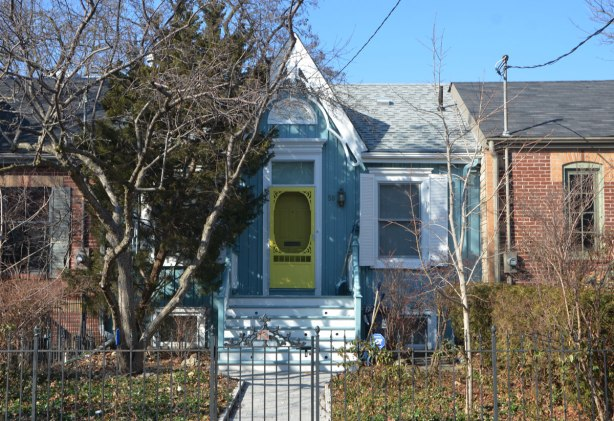 a gothic cottage painted pale blue with white trim,also a bright yellow front door.