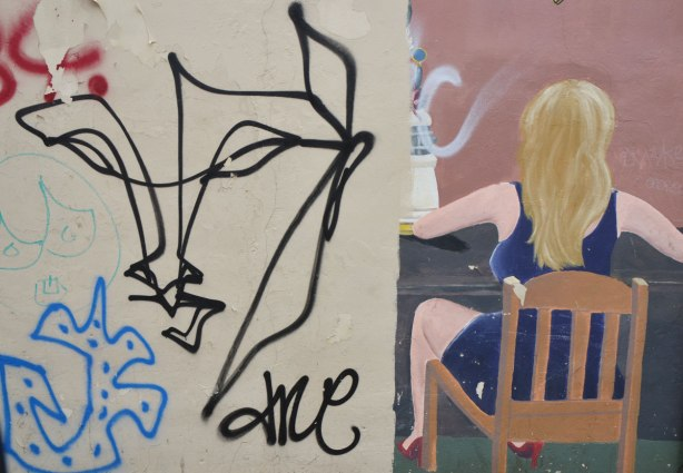 two pieces of street art, an anser face on one side, and a painting of a long haird blond woman sitting in a chair beside it, her back is to the viewer