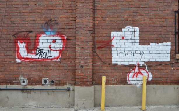 Two roughly drawn graffit animals on a wall, a duck and a whale, both in white paint with red details