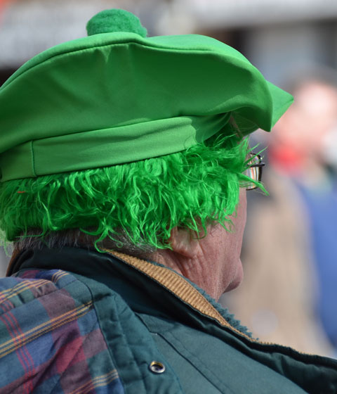 from the back, not much of his face is visible, a man wearing a green wig and a green tam with a pom pom on top