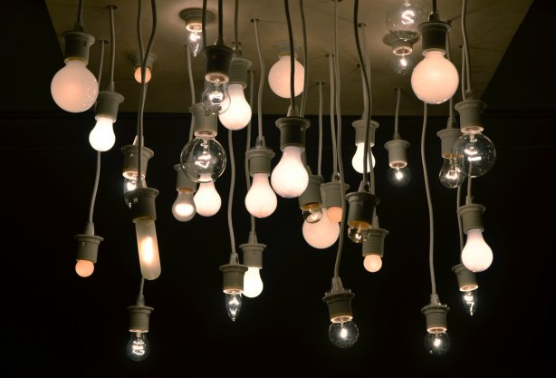 art installation on a gallery ceiling of many light bulbs of different shapes and sizes hanging from a piece of wood on cords of different, but short, lengths.