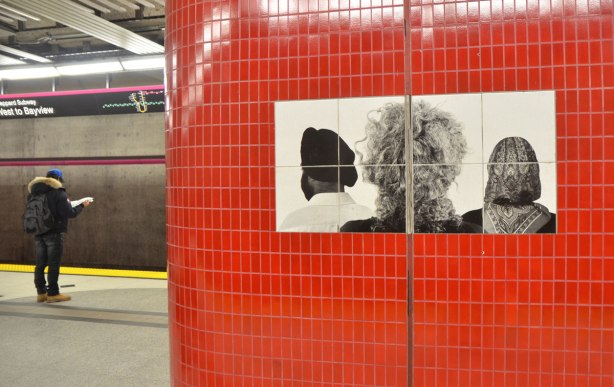 pillar covered in red tiles and with a black and white photo of the back of three peoples head, a man with a turban and a woman in a head scarf and someone with curly hair.