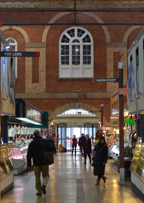 the interior of the St. Lawrence market, looking towards the north entrance, with the large arched window over the doorway