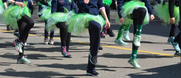 legs and feet of girls in frilly green tutus as they dance in a parade
