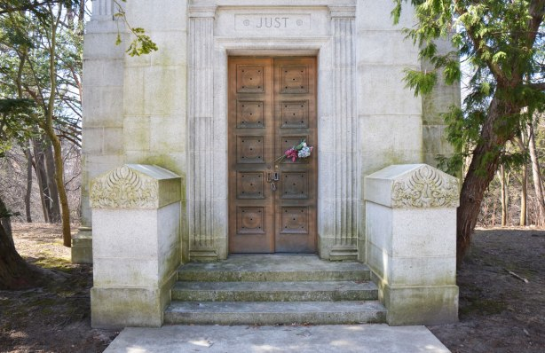 front of cemetery tomb for Just family, wood door with engravings on it.