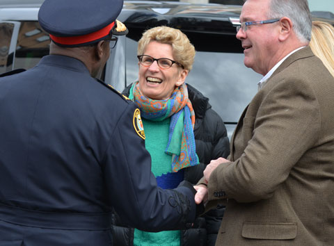 Kathleen Wynne, premier of Ontario, talks to a policeman and another man outside, before the start of a parade