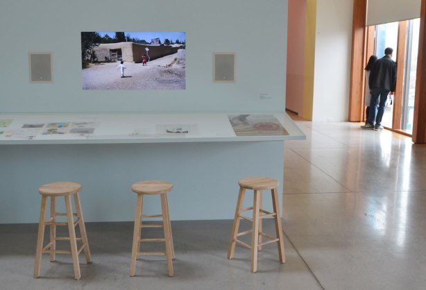 3 wood benches in front of a table mounted to a wall, art on the table, a video screen on the wall with a movie about kids in Afghanistan flying kites, some people in the background
