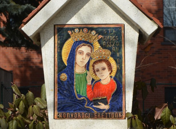 small picture of Mary and baby Jesus in bright colours, on a small shrine in front of a church